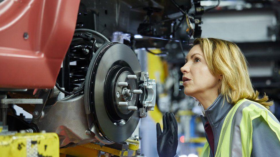 Female maintenance engineer examining car at factory