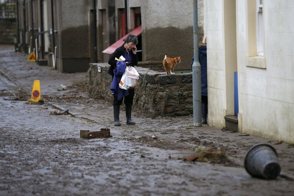A woman walks down a street covered in mud and debris after floodwaters subsided in Cockermouth