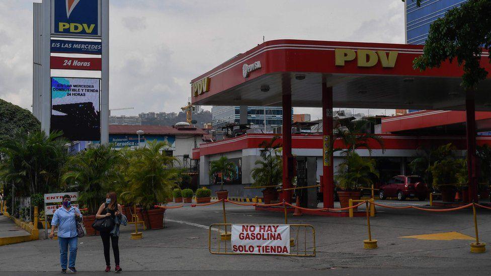 People walk past a closed petrol station in Caracas, Venezuela (14 May 2020)