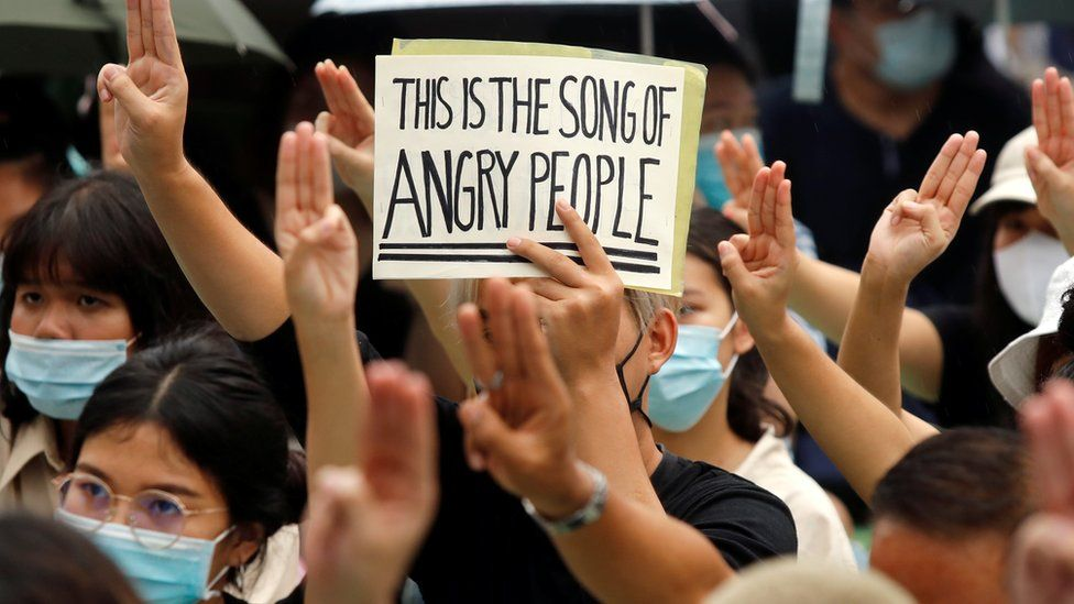 A protester holds a sign while doing a three-fingered salute during a demonstration to demand the release of activist leaders in Bangkok, Thailand August 8, 2020