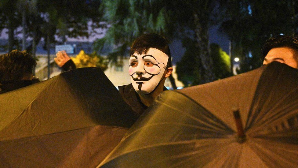 A protester looks out from behind some umbrellas in Hong Kong