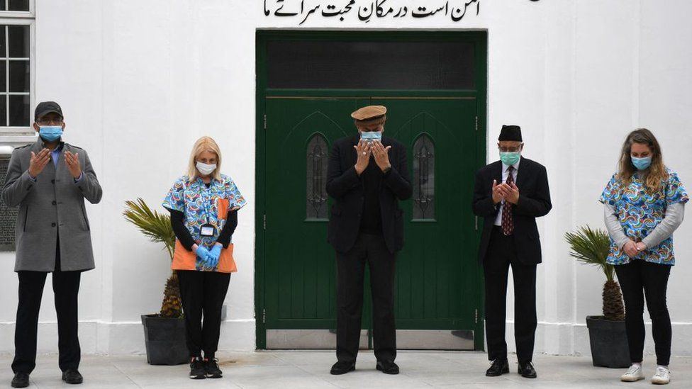 Health workers and faith leaders at the Fazl mosque vaccination centre take part in a minutes silence