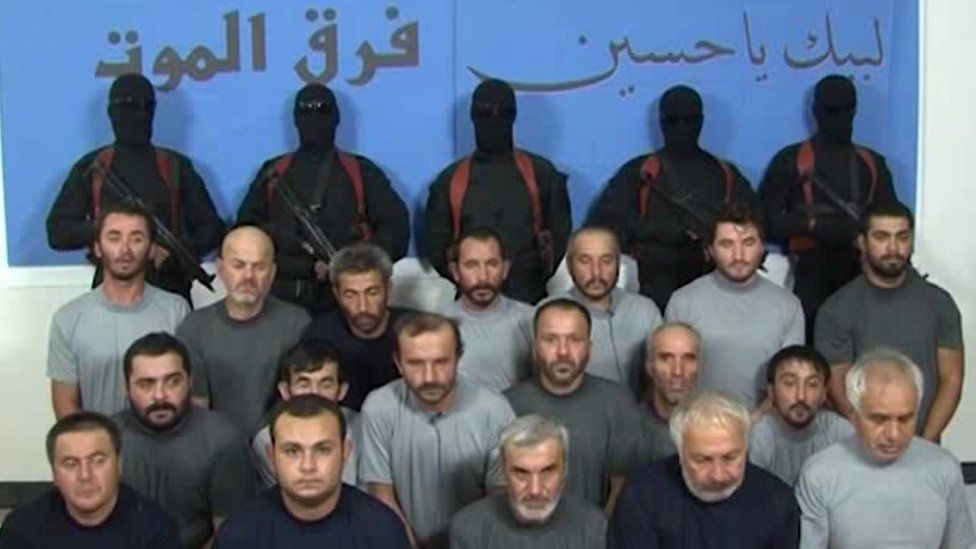"""Kidnapped Turkish construction workers appear in a video in front of masked gunmen and banner saying """"Death Squad"""" and """"We are at your service, Hussein"""" (11 September 2015)"""