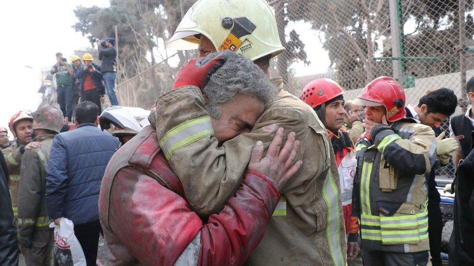 Firefighters react at the site of a collapsed high-rise building in Tehran, Iran (19 January 2017)