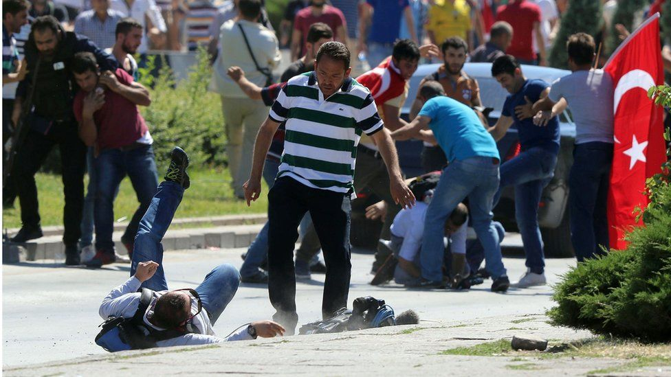 Supporters of Turkey's President Recep Tayyip Erdogan, who were staging a protest against a coup, clash with Turkish journalists near the Turkish military headquarters, in Ankara, Turkey, Saturday, July 16, 2016.