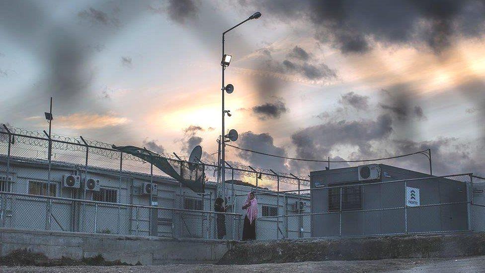 Women make phone calls inside the Moria refugee camp