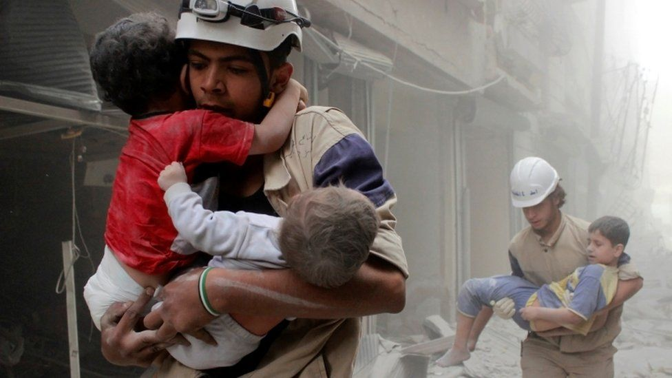 Members of the civil defence rescue children after an air strike by government forces in the al-Shaar neighbourhood of Aleppo