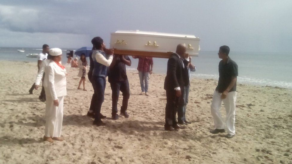 Coffin being carried on beach