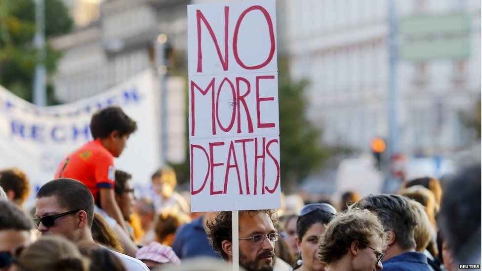 """A man holds up a sign reading """"no more deaths"""" at a rally in Vienna"""