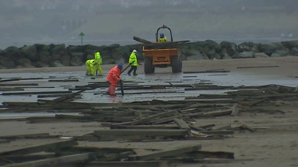 Engineers clean up the Colwyn Bay pier damage strewn across the beach