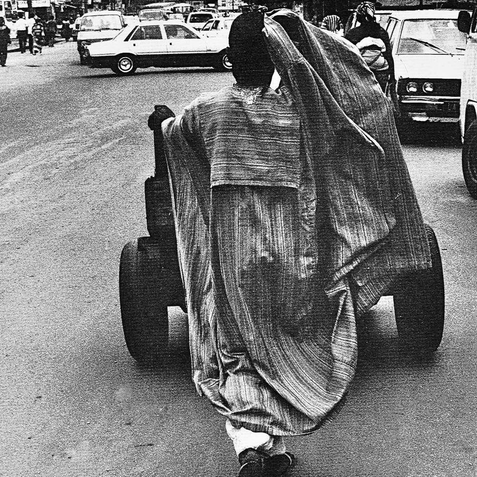 "A photo by Sunmi Smart-Cole entitled: ""Right Job, Wrong Attire"" - 1987 showing a man wearing a boubou pushing a cart"