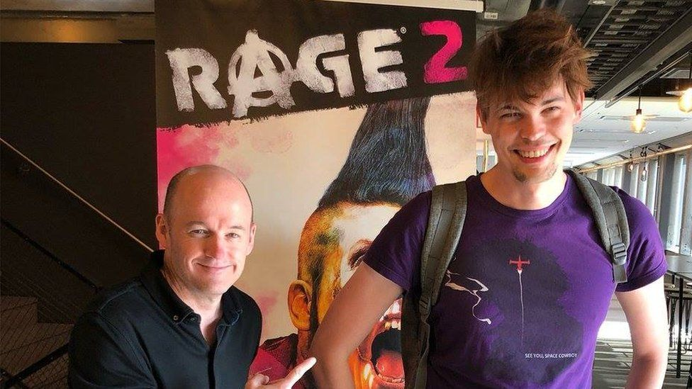 Javy is stands in front of a poster of the first-person shooter game Rage 2
