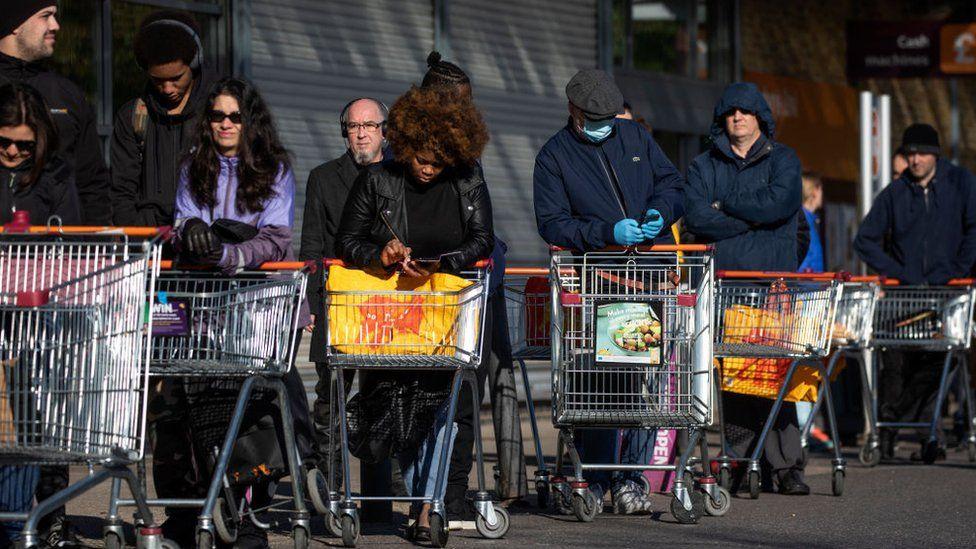 People queue outside supermarket