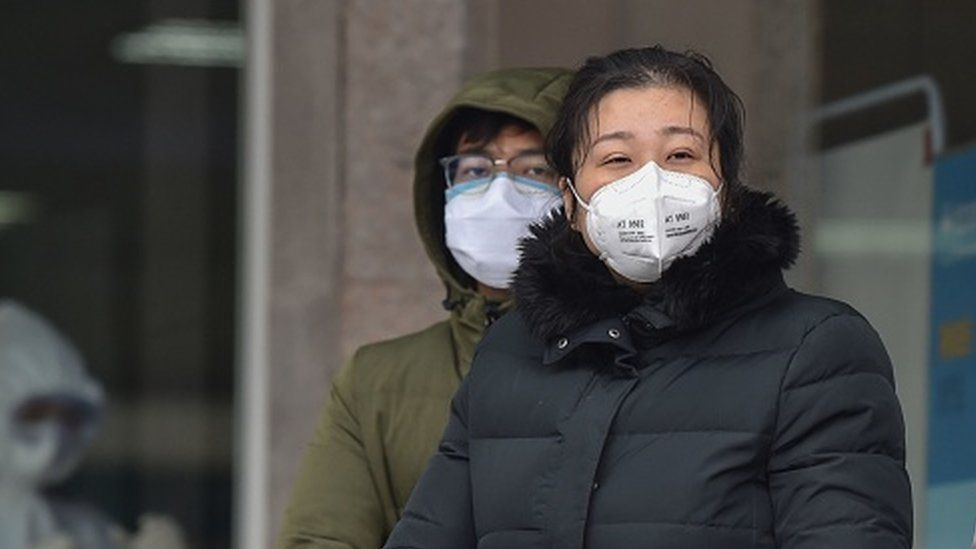 People wearing protective facemasks stand outside the Wuhan Fifth Hospital in Wuhan, China