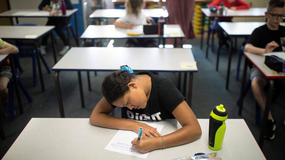 Girl sits at desk alone working after returning to socially distanced post-Covid-19 classroom