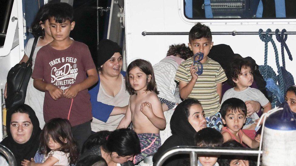 Italian Coast Guard and medical staff escort Iraqi Kurdish migrants off a Coast Guard patrol boat in the port of Crotone, Italy - 13 July 2018