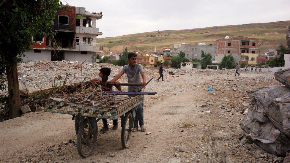Two children wheeling wood along a street in Cizre, Turkey - May 2016