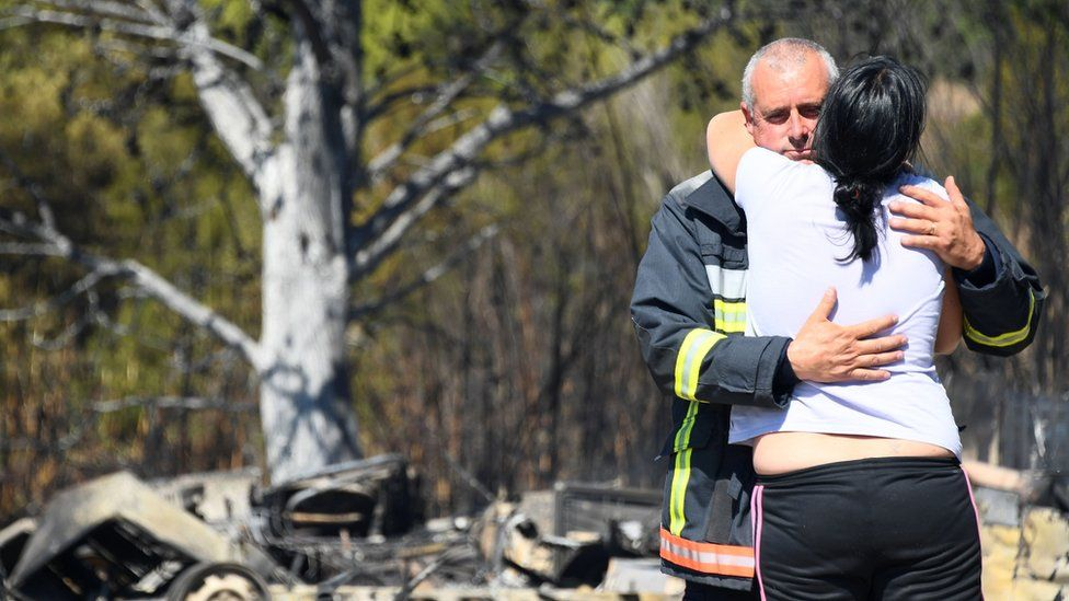 A woman is comforted by a firefighter as they stand amid debris following a fire in Bormes-les-Mimosas, south-eastern France, on July 26, 2017.