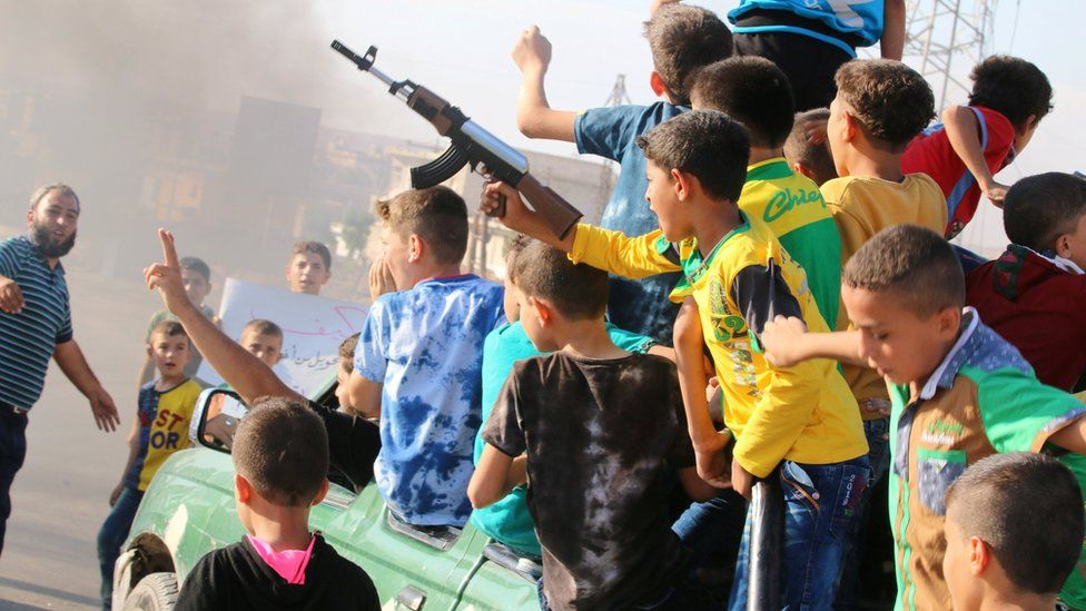 A boy carries a toy gun while riding a pick-up truck with other boys during a demonstration calling for aid to reach Aleppo near Castello road in Aleppo, Syria, September 14, 201