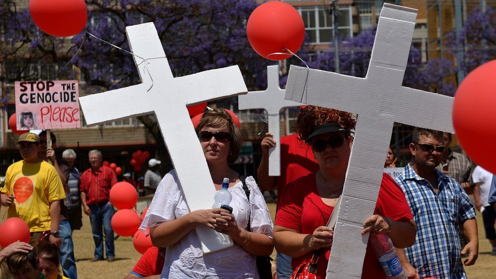 White South Africans holding balloons and crosses march to protest against the violent murder of farmers which they term 'genocide and oppressive state policies in favour of blacks' in Pretoria on October 10, 2013