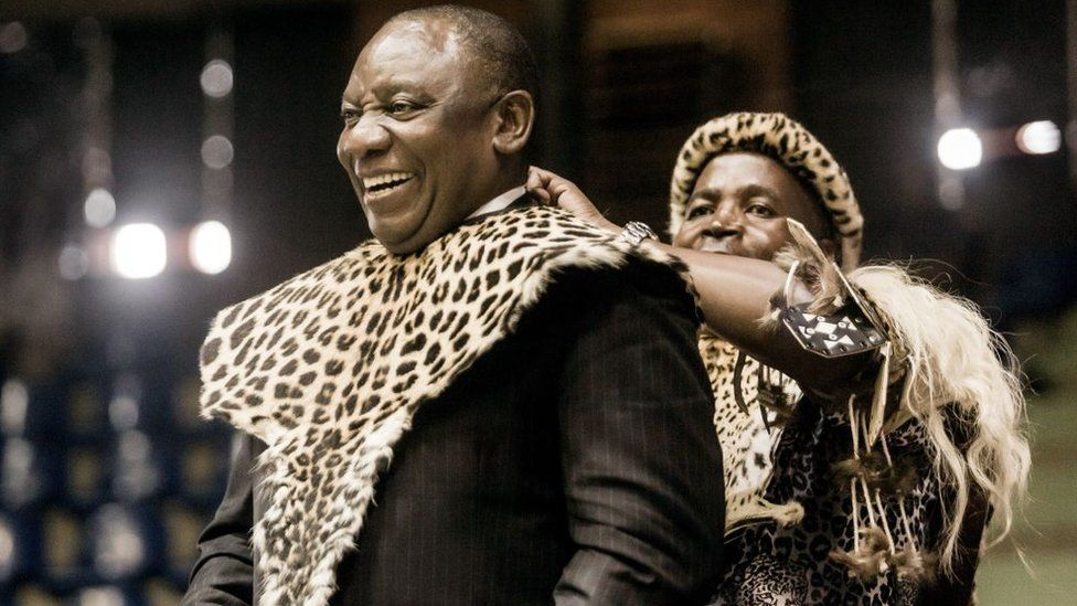 South African President Cyril Ramaphosa (L) smiles as he is adorned with a traditional Zulu attire as a gift from Inkosi (Chief) Mandla Mkwanazi in Empangeni, some 145 kilometres north of Durban, on October 14, 2018, during a ceremony to mark the successful transfer of land and ownership to the community following a land claim
