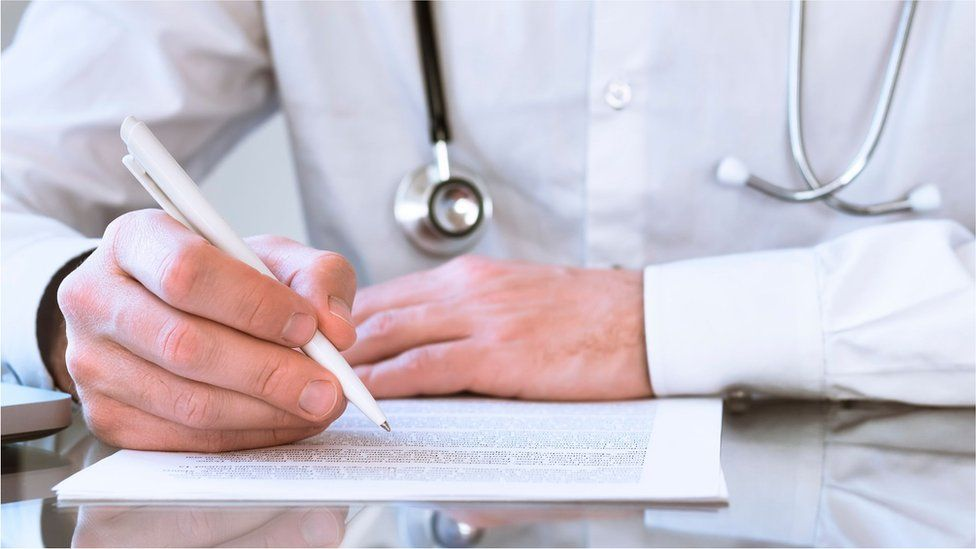 A doctor filling in a form