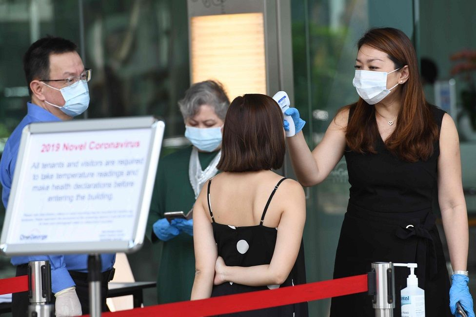Building management staff conduct temperature screenings of visitors and tenants of a building in the financial district of Singapore on 10 February 2020