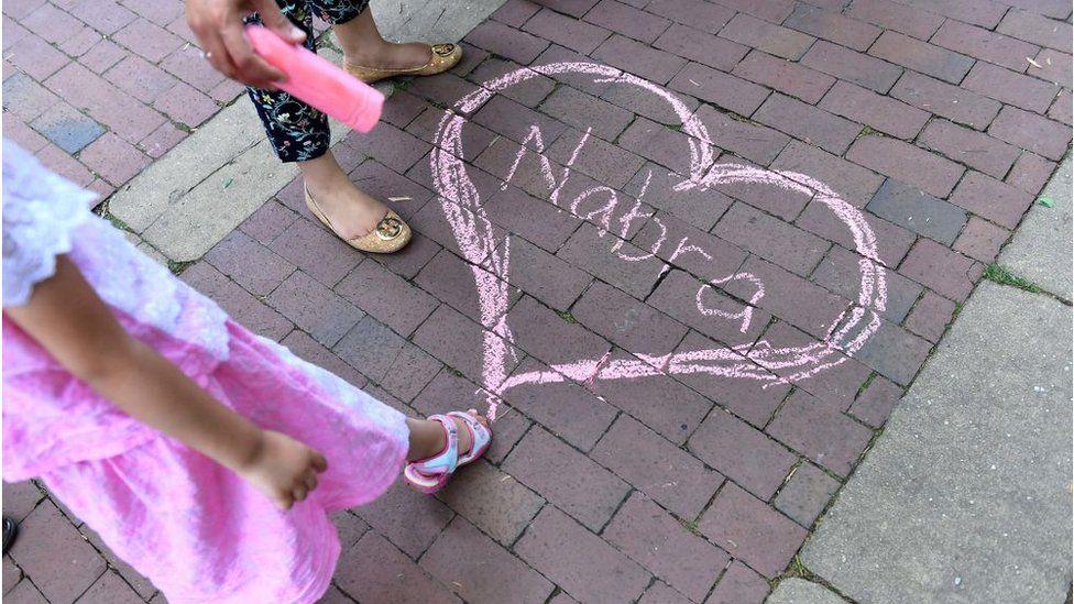 Nabra's name appears in chalk at a vigil for Nabra Hassanen at Lake Anne Plaza June 21, 2017 near Reston, VA