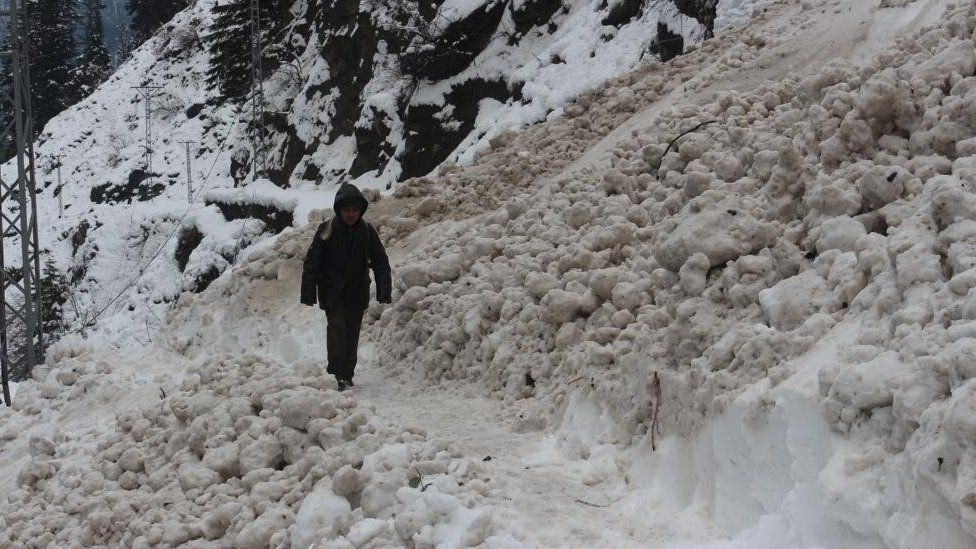 Boy walks in snow in Neelum valley - roads are cut off