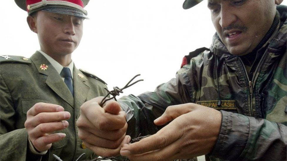 """This file photo taken on July 5, 2006 shows a Chinese soldier (L) and Indian soldier placing a barbed wire fence following a meeting of military representatives at the Nathu La border crossing between India and China in India""""s northeastern Sikkim state."""
