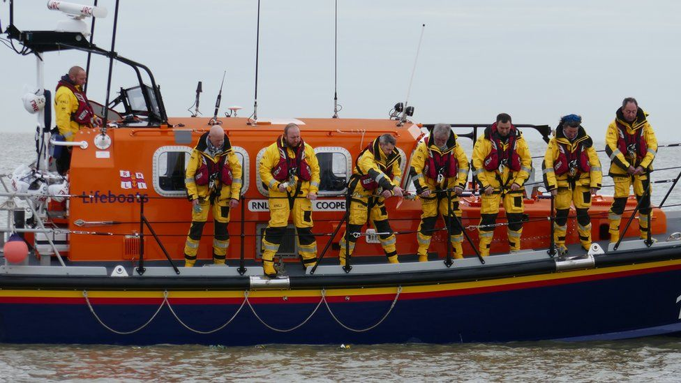The lifeboat crew drop flowers into the sea