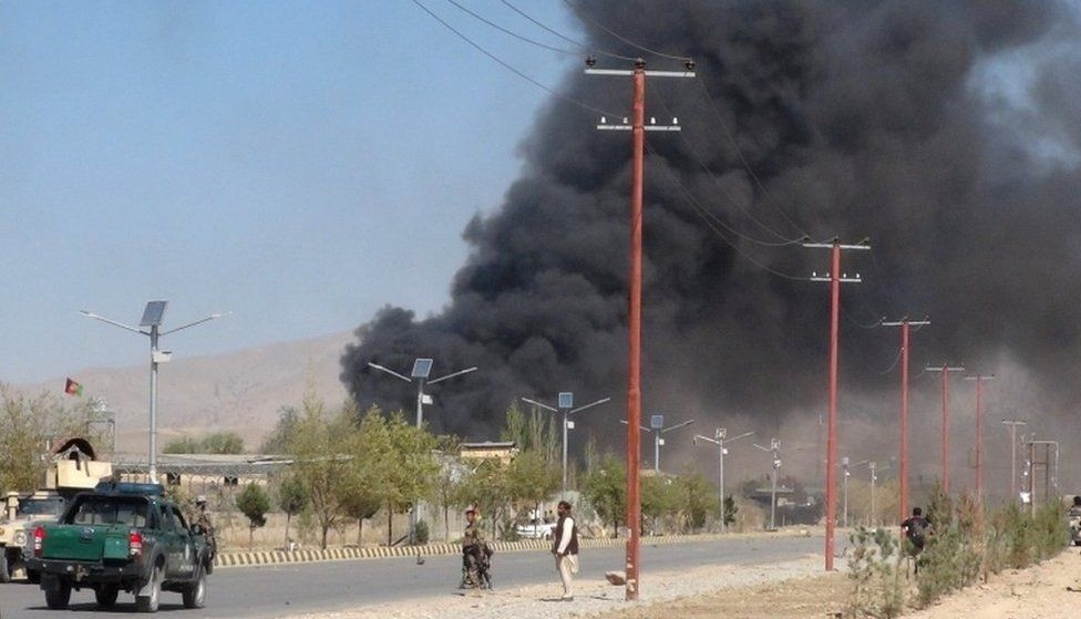 Smoke rises from police headquarters while Afghan security forces keep watch after a suicide car bomber and gunmen attacked the provincial police headquarters in Gardez, the capital of Paktia province, Afghanistan, on 17 October, 2017.