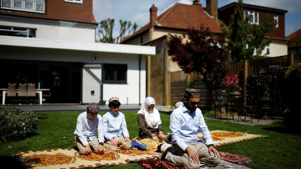 A family perform Eid prayers at home during the coronavirus pandemic