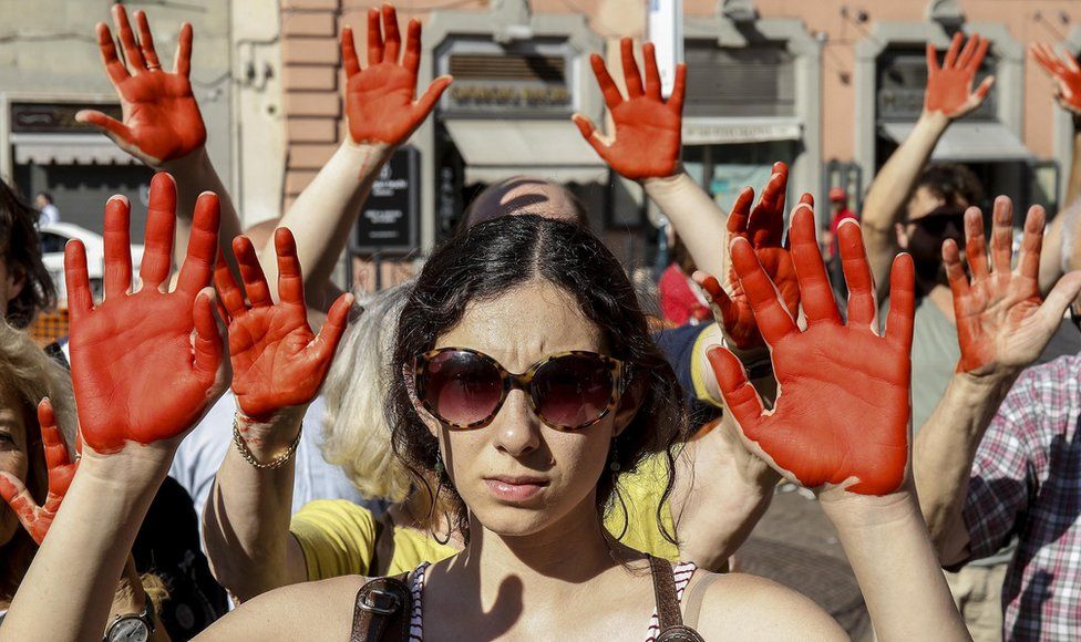 Protesters of Italys Radical Party with their hands painted red during a protest against the Italian Interior Minister Matteo Salvini