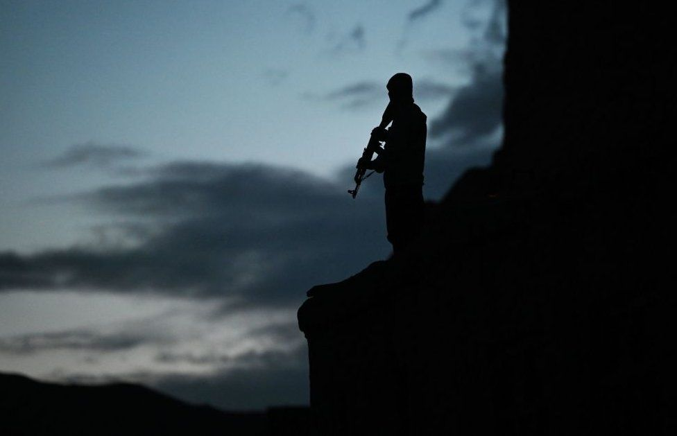 A policeman holding a gun silhouetted against a darkening sky