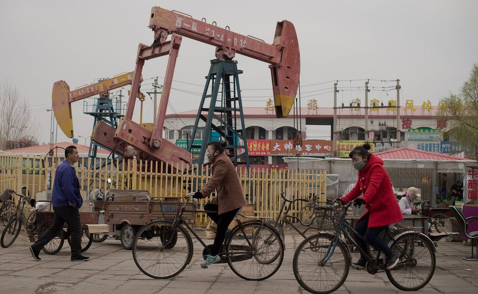 This picture taken on 2 May 2016 shows local residents riding bicycles next to oil pumps in Daqing, Heilongjiang province.