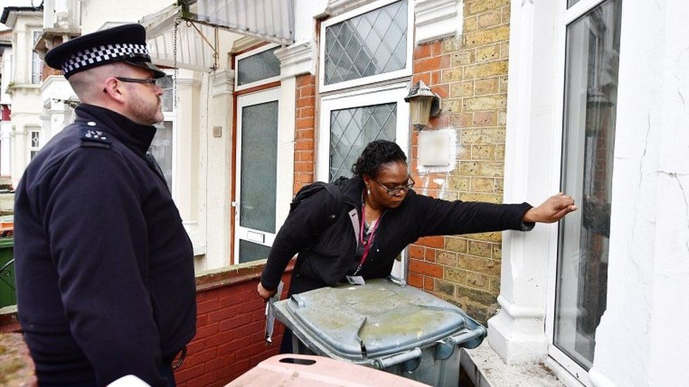 Police and a council enforcement officer conducting a raid