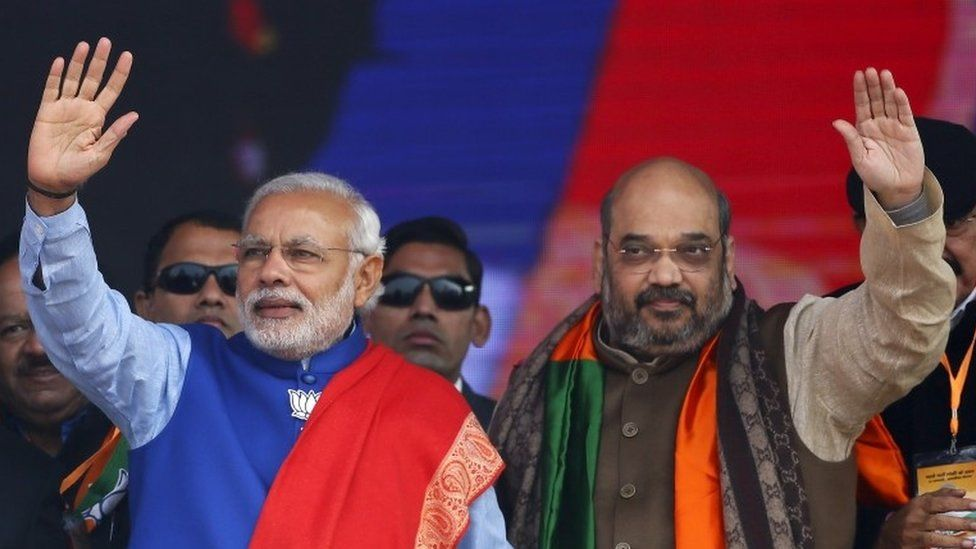 """Indian Prime Minister Narendra Modi (L) and Amit Shah, the president of India""""s ruling Bharatiya Janata Party (BJP), wave to their supporters during a campaign rally ahead of state assembly elections, at Ramlila ground in New Delhi in this January 10, 2015 file photo"""