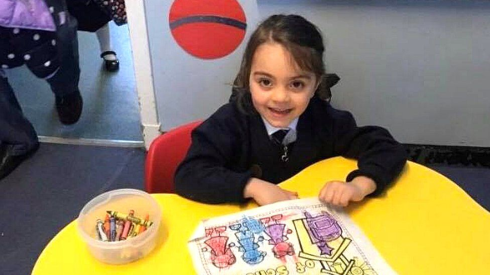 Mia Kasravi at a table in her school, drawing a picture with crayons