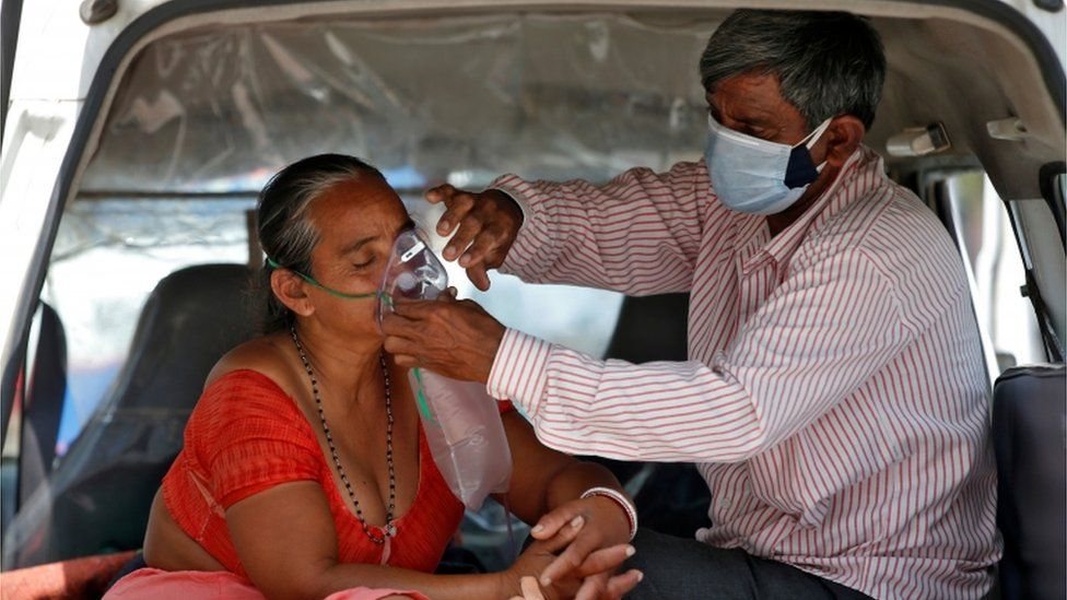 A man helps a woman with her oxygen mask