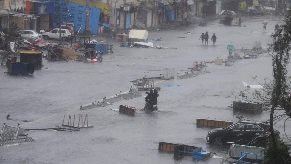People wade through floodwaters in Puri after Cyclone Fani hit