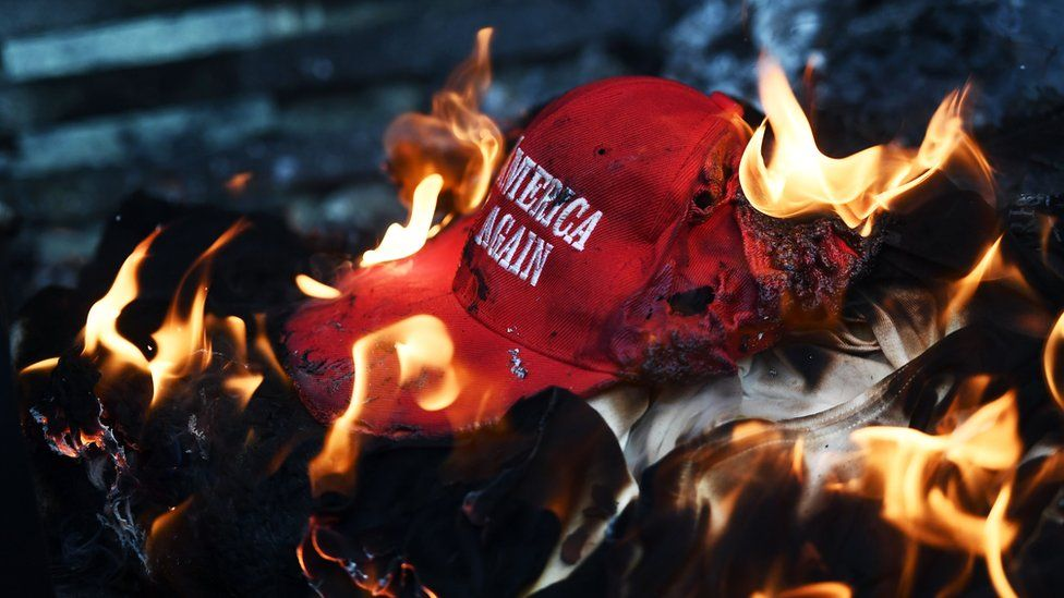 A Trump campaign hat set on fire by protesters during demonstrations in Washington