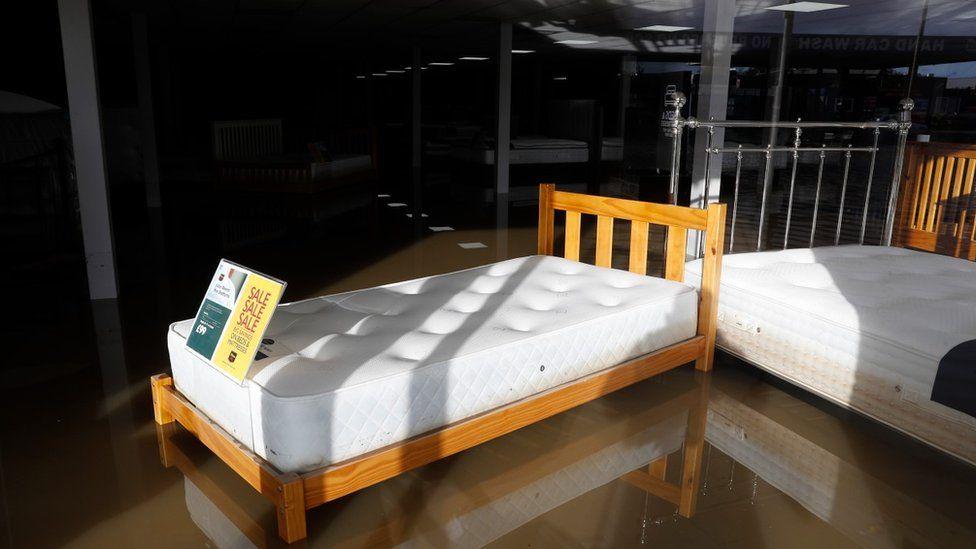 Një shtrat në dritaren e një dyqani qëndron në ujërat e përmbytur
