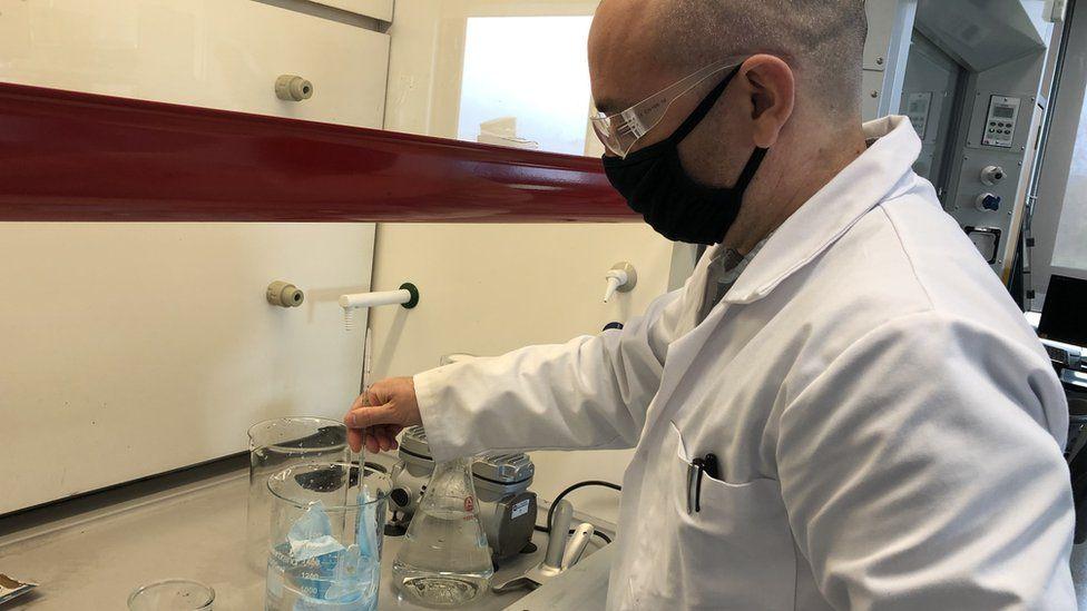 Plastic mask stirred in liquid in Swansea University laboratory