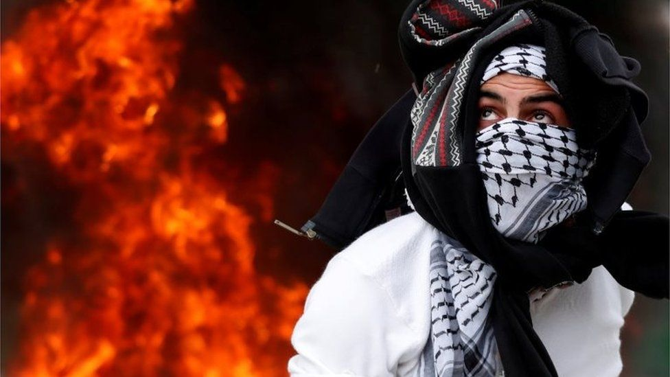 Masked Palestinian in front of flames in Ramallah (20/12/17)