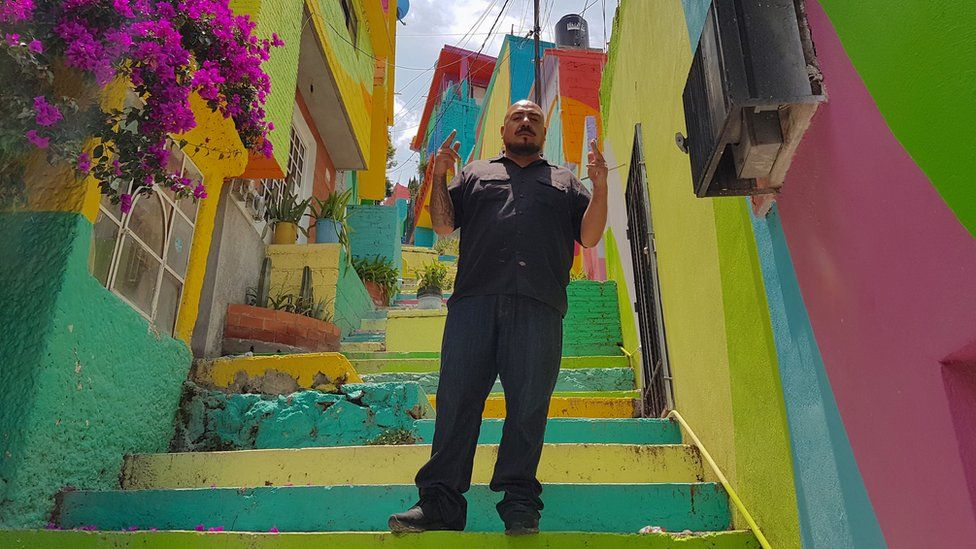 Enrique Gómez poses in a colourful alley in
