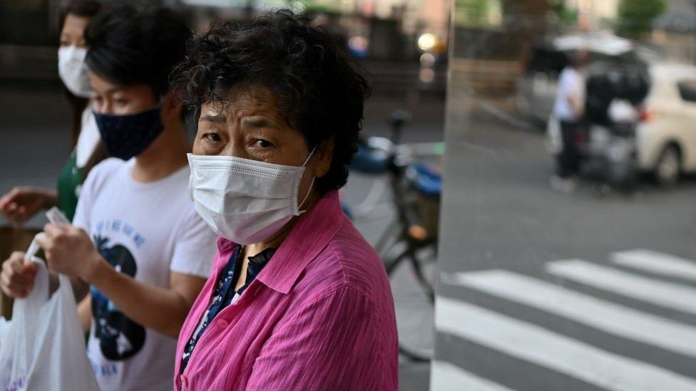 An elderly woman wearing a face mask walks in a street in Tokyo on June 9, 2020.