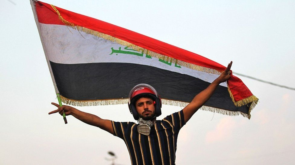An Iraqi protester poses with a national flag during a demonstration in Baghdad on 29 October 2019