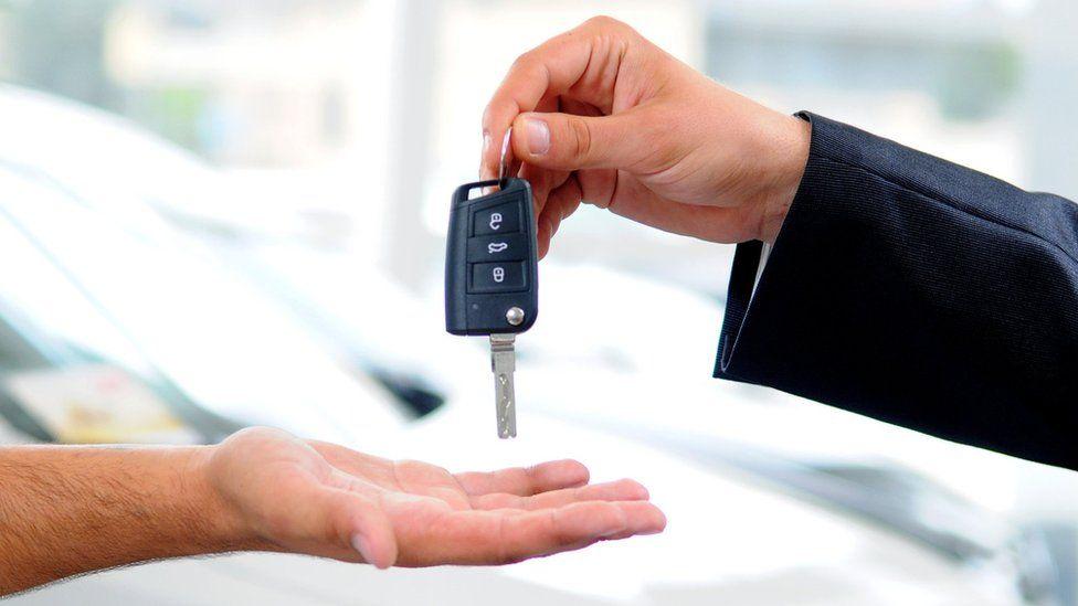Salesman hands over car key