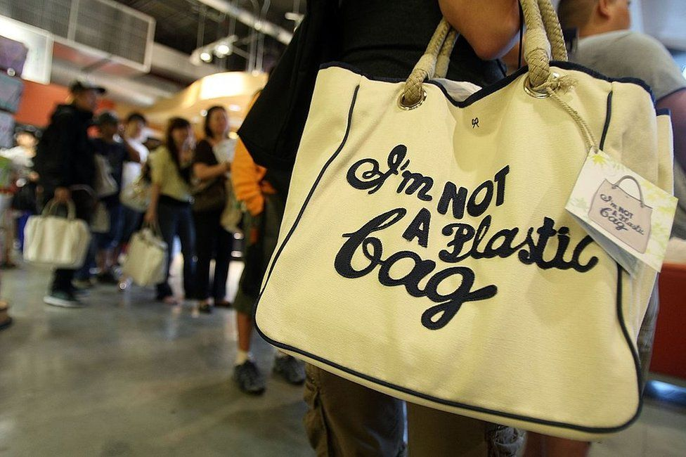 A customer holds a shopping bag designed by Anya Hindmarch which reads 'I'm Not a Plastic Bag'